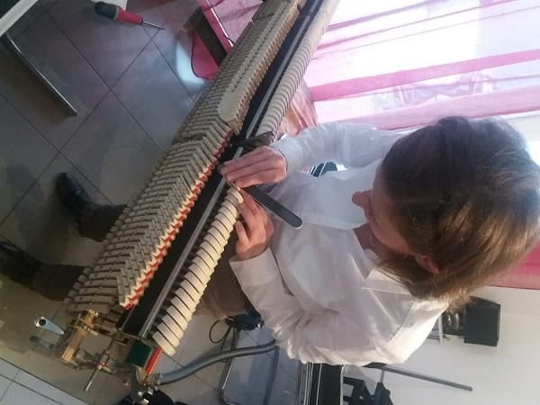 Agnès Nitelet règle la mécanique d'un piano - ponçage des marteaux